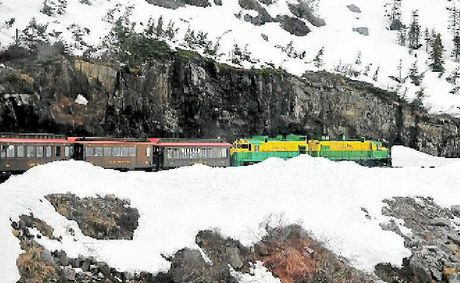 The train makes its way through snow studded mountains as it descends from the summit of White Pass.
