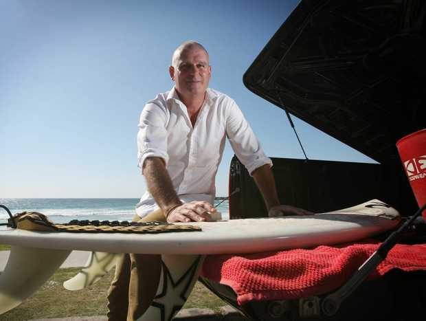 Scoot's surfing general manager Darren Wright waxing up for a before work at Duranbah.