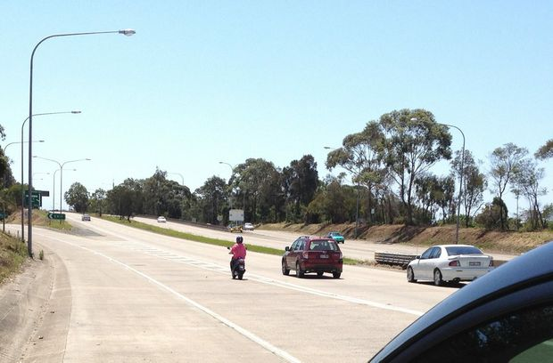 A scooter rider braves the Pacific Hwy after Terranora Creek bridge.