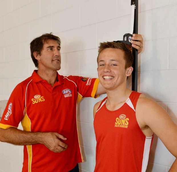 Former AFL player and member of the Gold Coast Suns development team Craig Starcevich measures up Jordan Harding.