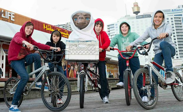 Young local riders from the Sydney BMX club help E.T. arrive at Madame Tussauds in Sydney.