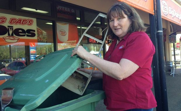 Withcott Newsagency owner Sue Case tidies up the front of her shop.