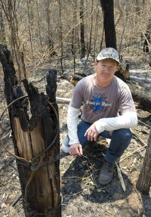 Andrew Barnes inspects fire damage to his property east of Crows Nest yesterday.
