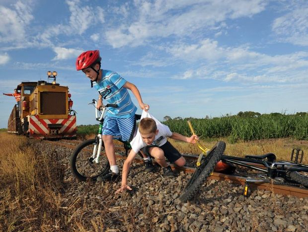 CLOSE CALL: Bundaberg Sugar are reminding parents to make sure their kids are not playing near cane railway tracks as this year's crushing season has been extended. Austin and Duncan Allen helped to illustrate the dangers in a photo set up by Bundaberg Sugar and the NewsMail. Photo: Max Fleet / NewsMail