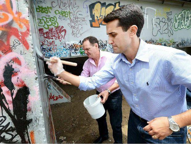 CLEAN-UP: Local Government Minister David Crisafulli (front) and Mayor Paul Pisasale remove graffiti from David Trumpy Bridge.