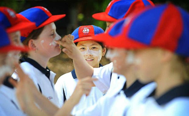 PAINT TIME: Claudia Tran, 11, of Sydney East, framed by her team-mates as they apply sunscreen before taking part in the Primary School Sports Association cricket carnival in Lismore.