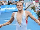 Peter Kerr celebrates in style as he crosses the line to win the men's 2012 Noosa Triathlon title yesterday.