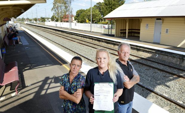 Debby Burns holds a petition with Jo Kennedy and Bob Barrett. The train passengers are disgusted at the behaviour of some younger passengers on the Ipswich to Rosewood train service. Between the three of them they have experienced abusive language and been spat on.