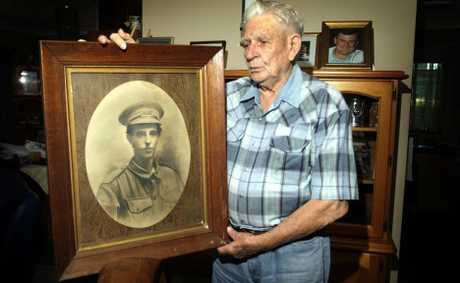 Alf Porter looks at a photo of his father from about 1915 when in was enlisted in the Australian Imperial Force.