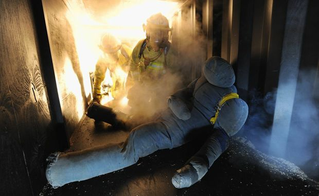 Hervey Bay firefighters Tim Loague and Luke Young make their way through a training simulator to rescue a mock house fire victim.