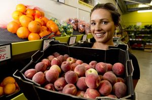 Wray Organic worker Elisabeth Kent shows off some of the store&squot;s first locally-grown peaches of the season.