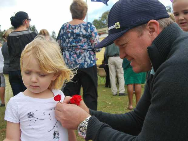 Simon Phillips pins a poppy on daughter Sadie at the Pottsville Remembrance Day on Sunday.
