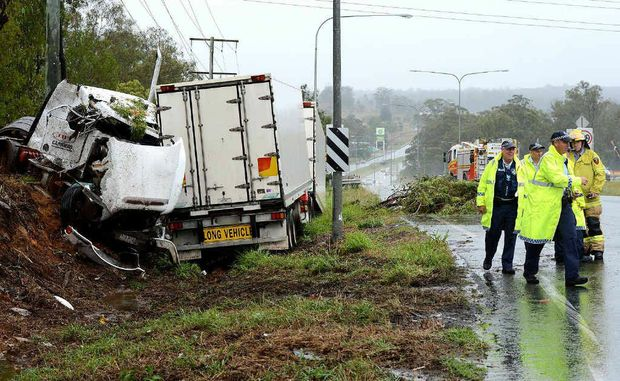 CLEANING UP: Emergency services deal with the aftermath of a crash involving a refrigerated semi-trailer on the Warrego Hwy at Blacksoil on Saturday morning.