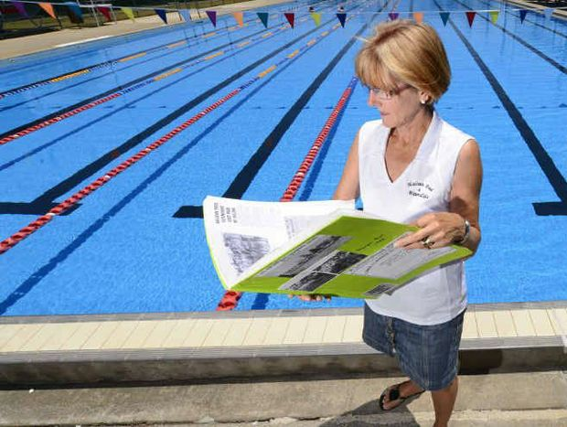 Robyn Clarke looks over a scrapbook of the history of the Maclean Pool.