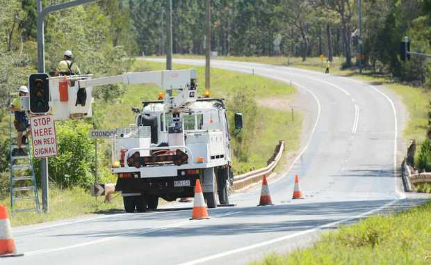 Workmen remove the temporary traffic signals on the Tin Can Bay Rd at Coondoo Creek bridge yesterday.