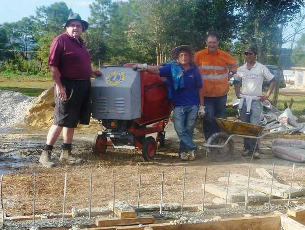Terranora Lion Peter Maroney, fellow MiVAC volunteer Michael Weibler and locals Vang and Mua with the mixer. Photo: Contributed