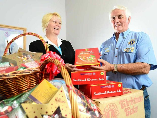 FESTIVE TREAT: Lowood Lions Club president Kevin Larsen hands over fundraising Christmas cakes to Stitt and St George Funeral Directors branch manager Alison Crabtree.
