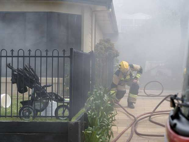 A firefighter battles a blaze at a Currawong St home in Rangeville.