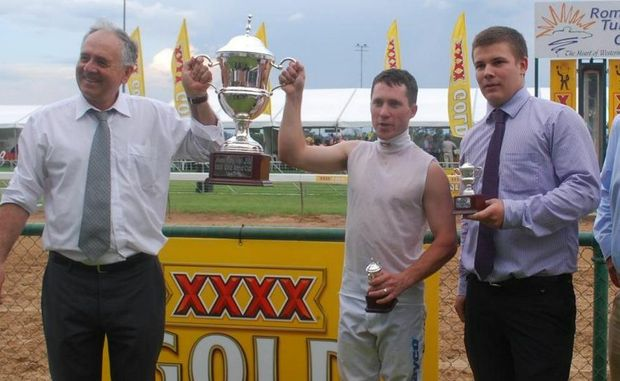 Co-owner Anselmo Morosini of Toowoomba, jockey Adam Best and Ben Dosey (representing trainer Michael Nolan) celebrate Blow a Kiss's win in the 2012 Roma Cup.