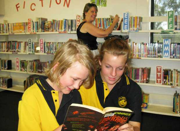 BOOK BUDDIES: Harley Zardani and Angel Kahler check out a book in the Tivoli State School library while librarian Julie Langlands looks on.