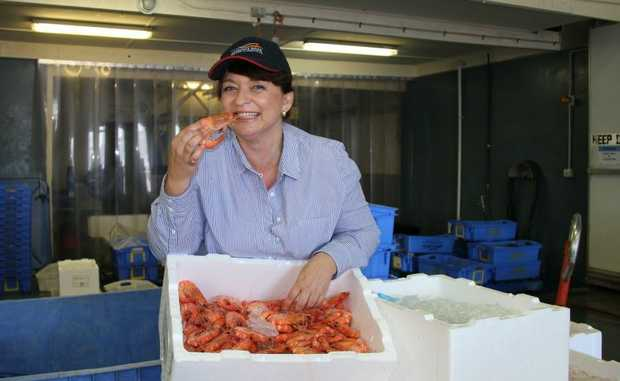 GOOD CATCH: New Clarence River Fishermen's Co-operative general manager Danielle Adams gets playful with some delicious Yamba prawns. Photo: Rodney Stevens/Daily Examiner