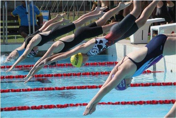 Kala Rideout (yellow cap) dives off the block during last weekend's carnival. Karla took out the 13 girls Age Champion title at the meet. Photo Contributed