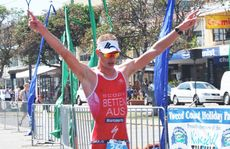 Crossing the finish line, an exhausted Samuel Betten who took out the Olympic Open Men's section at the Kingscliff Triathlon.