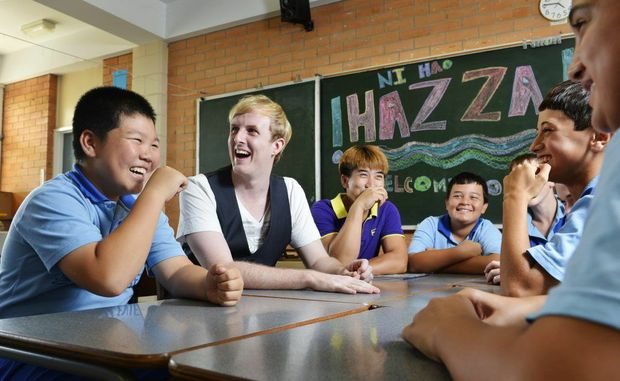 """Chinese pop sensation Harry Harding """"Hazza"""" shares a joke with Raceview State School students including Michael Chen (left) and Michael's father, who recently migrated from China."""