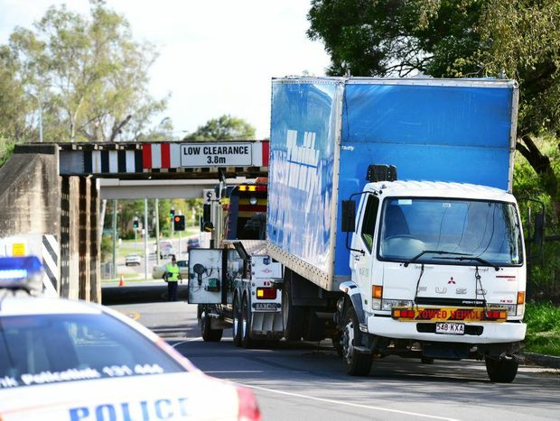 A tow truck prepares to remove a hire truck that struck the railway bridge on Layard Street in Goodna.