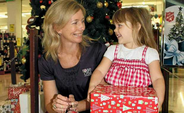 Rose City Shoppingworld marketing manager Louise de Lissa and Lucy Read, 3, place some gifts under the Wishing Tree.
