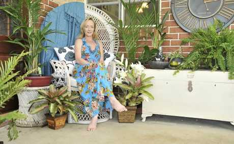 Hollie Butlin sitting in a peacock chair that she sells at her shop.