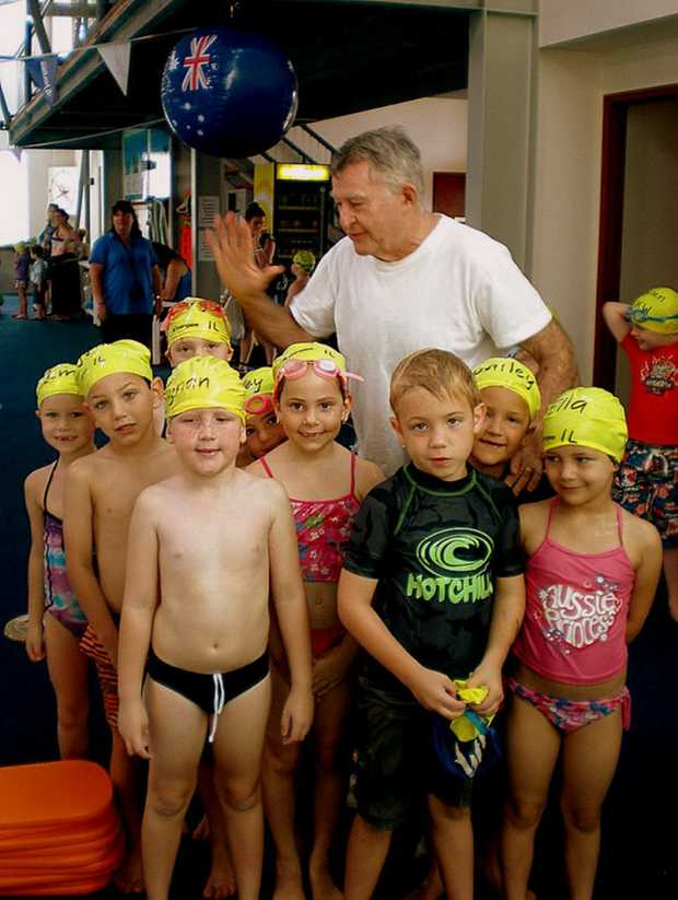 Laurie Lawrence congratulates Centaur swimmers with a group high five. Photo: Contributed