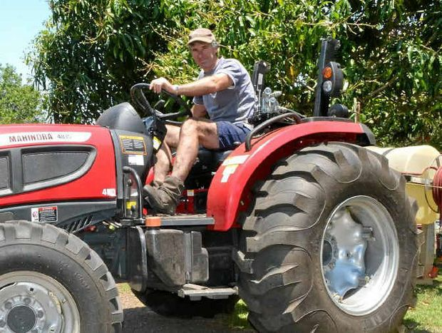 BE PREPARED: Macadamia farmer Greg Bennett on the tractor he used to help the Rural Fire Service put out spot fires.