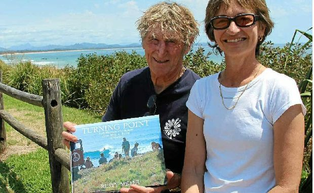 SURF LEGEND: Rusty Miller and Tricia Shantz with their new book at Byron Bay's Main Beach.