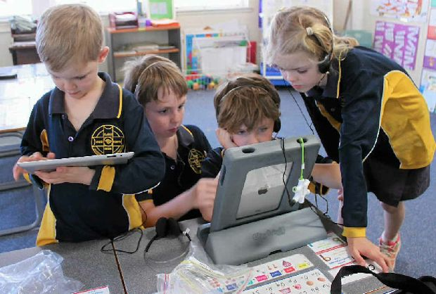 SNAIL'S PACE: Clarke Creek State School students Cameron Hill, 6, Max, 9 and Franko Deveson, 7 and Lydia Hill, 9, use the school iPads but internet speeds limit what they can do online.