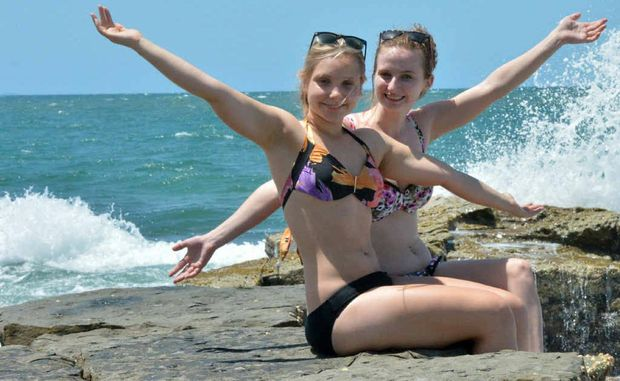 Jacinta McLeod and Shannen Pretlove, of Caboolture, cool off at the beach.