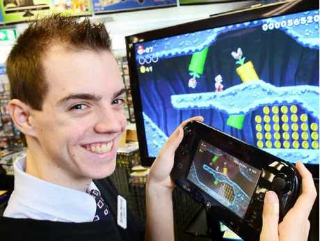 BIG STEP UP: Harvey Norman Ipswich salesman Chris Malone test drives the Wii U.