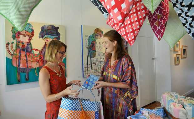 Loading up a shopping bag is (left) Blockwork Gallery director Sally Johnston, with Feather & Buzz co-owner Anna Chandler. The online store will be selling their goods at a pop up shop at the gallery tonight and tomorrow.