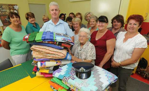 Senior Sergeant Dan Willett accepts 22 quilts for Police Legacy from Hervey Bay Social Quilters including the group's oldest member Joyce Murphy.