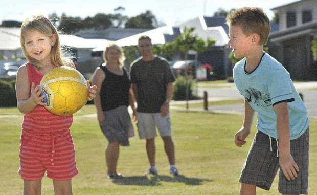 From left, Summer (5) and Reid (7) Thompson testing their ball skills. (at the back mum and dad : LTR Tina and Craig Thompson) of East Ballina. Photo Mireille Merlet-Shaw / The Northern Star