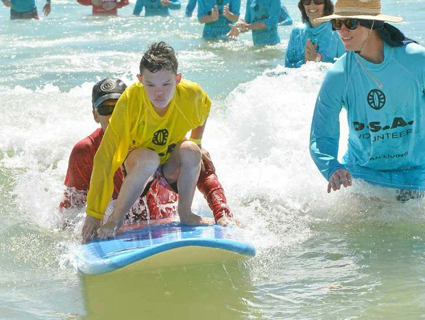LOVING LIFE: Laura Kokavec, 12, is a picture of concentration at the disabled surfing lessons on Maroochydore Beach yesterday. Look at the joy on the faces of the volunteers behind her.