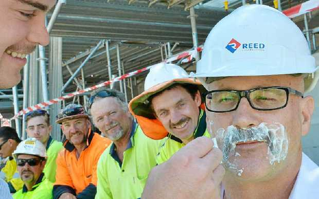 OFF WITH THE FUZZ: Tim Reed shaves RCQ project manager Ross Webb while workmates wait in line for the soap and razor.