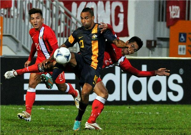 Archie Gerald Thompson fends off Hong Kong defender Lee Chi Ho during the EAFF East Asian Cup 2013 Qualifying match between Hong Kong and Australia at Mong Kok Stadium on December 3, 2012 in Hong Kong.