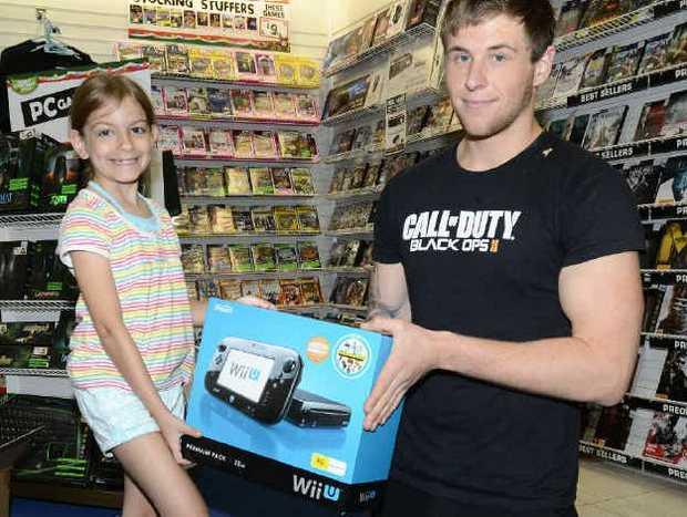 Grafton Shopping World EB Games manager Brian Ryan shows seven- year-old customer Angel Marre Hawkins Ford the new W11-U console. Photo Debrah Novak