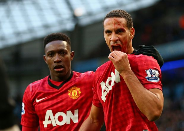 Rio Ferdinand of Manchester United is helped by team-mate Danny Welbeck (L) after being struck by an object during the Barclays Premier League match between Manchester City and Manchester United at Etihad Stadium on December 9, 2012.