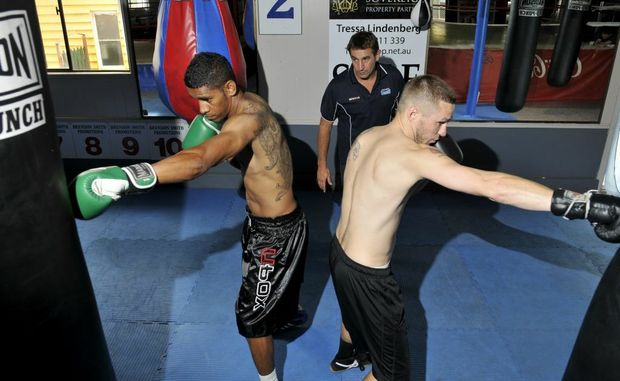 Brisbane-based boxer Sammy Leone (left) and Englishman Darren Askew working out with trainer Brendon Smith this week.