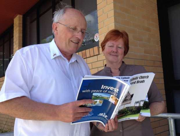 Father John Darbyshire and Di Millar reading a few facts about the church's history.