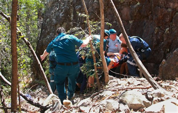Paramedics and friends of the injured climber move him so that he can be better accessed by the helicopter.