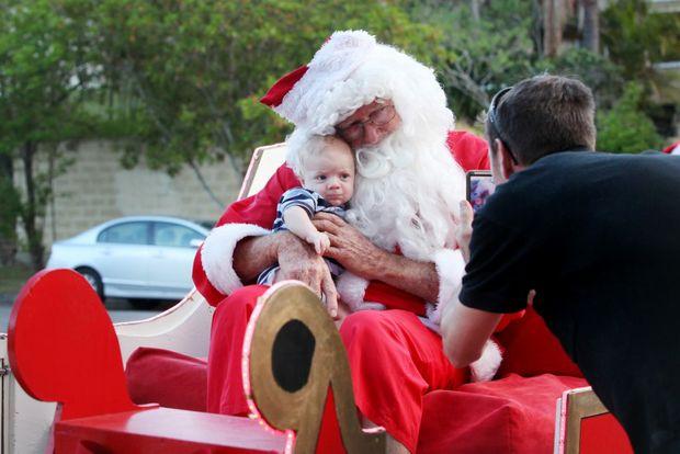 Michael Cramer taking 13-week-old Levi to visit Santa in his sleigh at Jindalee. Photo: Inga Williams / The Satellite