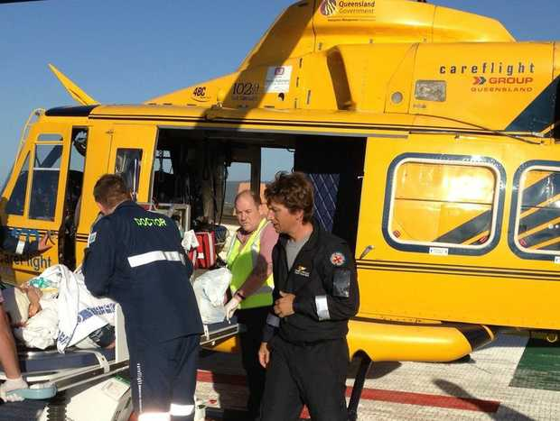 The RACQ CareFlight crew prepare to airlift a woman who sustained a fractured skull and brain bleed after a fall at a pub.